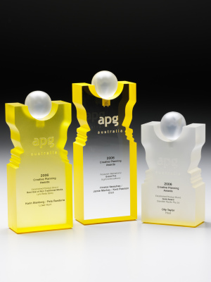 APG - Custom acrylic shape with embedded metal logo in ball. Coloured yellow. 220 mm