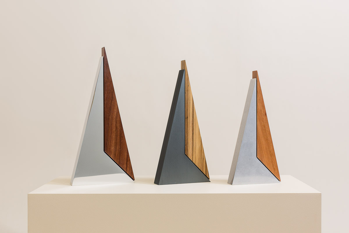 Large Peak with highly polished finish and Red Iron Bark timber, Medium Peak with brushed charcoal anodised finish and Spotted Gum timber, Small Peak with vibration stone polished finish and .